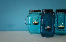 Vintage Decorative Magical Mason Jars With Candle Light On Wooden Table