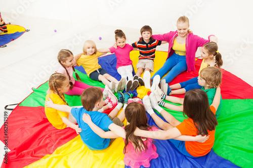 Pinturas sobre lienzo  Happy children playing circle games with teacher
