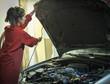 Female mechanic lifting hood of car