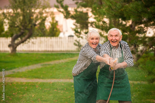 Old couple having fun. Happy people with garden hose.