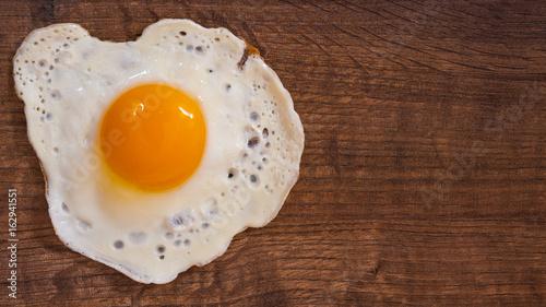 Fotografie, Obraz  Fried egg on the brown wooden table background