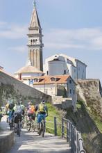 Rear View Of Bikers Biking Towards Church