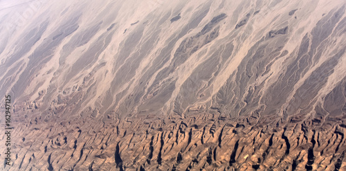 Desert with brown rugged terrain and sand barchan dunes Canvas Print