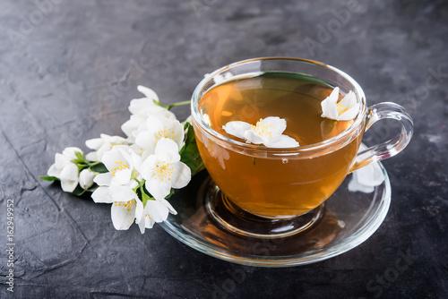 Cuadros en Lienzo Cup of tea and jasmine flowers on a dark concrete  background