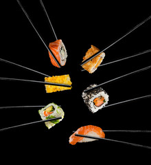 Fototapeta Sushi pieces placed between chopsticks, on black background