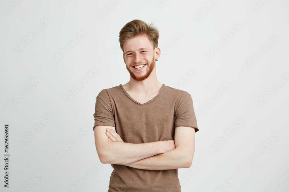 Fototapeta Portrait of happy cheerful young man with beard smiling looking at camera with crossed arms over white background.