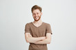 canvas print picture - Portrait of happy cheerful young man with beard smiling looking at camera with crossed arms over white background.
