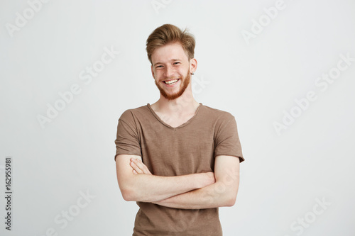 Obraz Portrait of happy cheerful young man with beard smiling looking at camera with crossed arms over white background. - fototapety do salonu