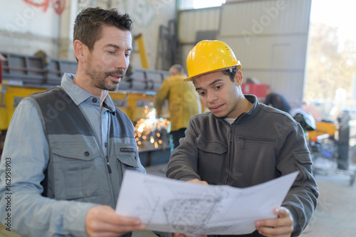 Canvas Prints Textures male factory worker and supervisor are analyzing plans