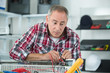 mid-adult male plumber repairing radiator