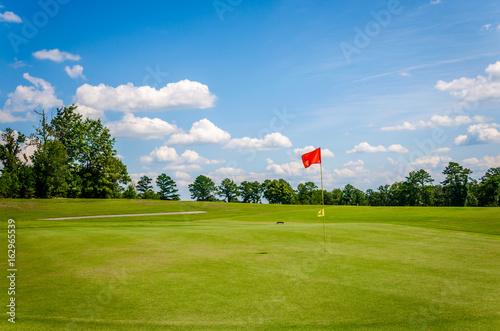 Plakat Pole golfowe z piękną zieloną trawą, błękitnym niebem i białymi chmurami puffy. Rekreacyjna aktywność sportowa w golfie.