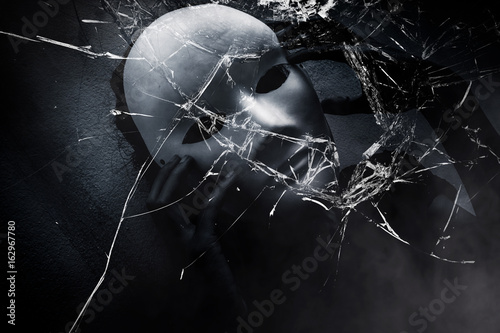 Mysterious woman in black wearing white mask hidden shattered glass ,Scary backg Canvas Print