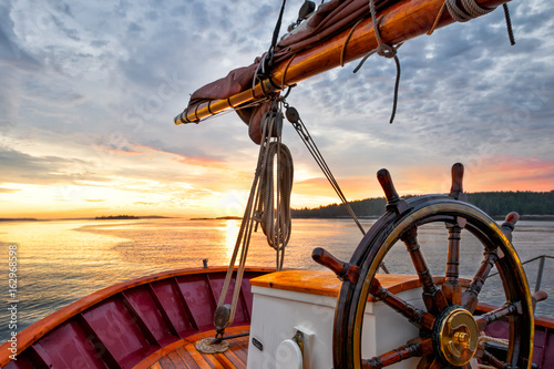 Sunrise sailing on a tall ship schooner. Close up of steering wheel, bow and boom against a dramatic sky at dawn.