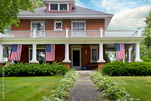 Fotografia, Obraz  American flag decorations on front porch of old brick home