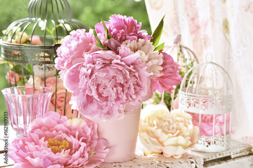 peony bunch in vase on the table in the garden with color effect