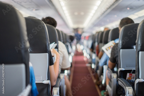 Türaufkleber Flugzeug passenger seat, Interior of airplane with passengers sitting on seats and stewardess walking the aisle in background. Travel concept,vintage color