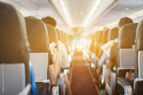 Tuinposter passenger seat, Interior of airplane with passengers sitting on seats and stewardess walking the aisle in background. Travel concept,vintage color
