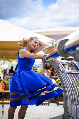 Fotografía  Blond hair curly woman plus size european appearance in blue flying retro dress
