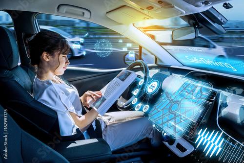 Fotografiet  young woman using a smart phone in a autonomous car