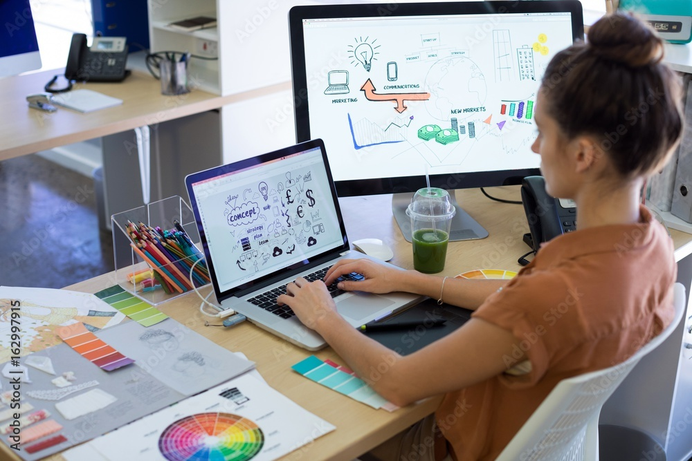 Fototapeta Female executive working over laptop at her desk