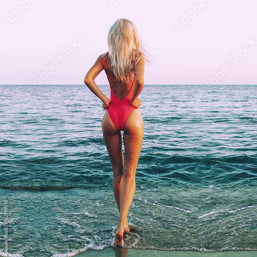 Fotografie, Obraz  Slim and athletic girl in a swimsuit on the beach