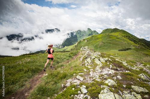 Plakat młoda kobieta działa samodzielnie na ekstremalnych przygody ultra trail z wysokogórskiej scenerii i błękitne niebo