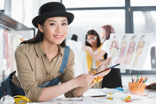 Fotografie, Obraz  portrait of cheerful fashion designer looking at camera while showing sketch