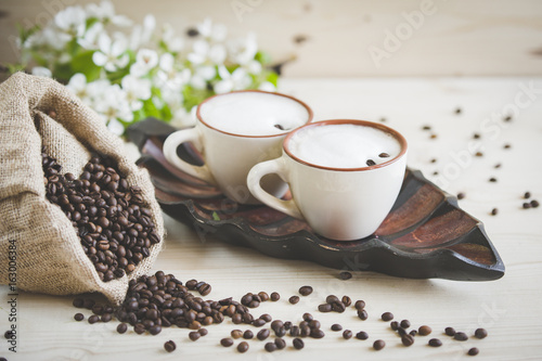 Wall Murals Cafe Two cups of freshly brewed, frothy cappuccino. Spilled coffee grains, chocolate and cane sugar. Theme of coffee, cappuccino, mocha chino, america no. Beautiful elegant background with place for text