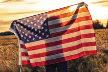 Silhouette Of Young Woman Holding USA Flag In Field At Sunset