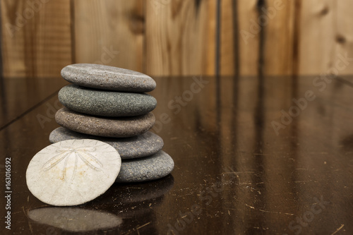 Fotografia, Obraz  Granite Rocks and a Sand Dollar stacked on an antique mahogany table