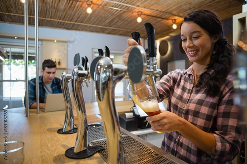 Young barmaid pouring beer from tap in glass Canvas Print