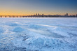 Beautiful winter landscape with frozen river and sunset sky.