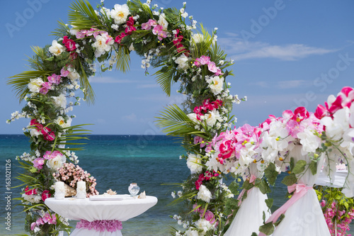 Fototapety, obrazy: Wedding arch with pink and lilac flowers and table with accessories on the caribbean seashore in summer sunny day