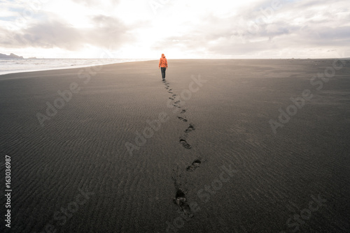 Fotomural Guy in Iceland walking on empty black sand beach into sunset leaving footprints