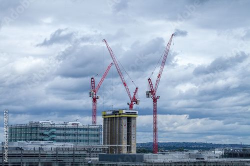 Photo  High rise building construction with red cranes over London.