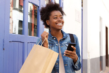 Beautiful African Woman Walking With Shopping Bag And Smart Phone In City