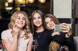 Three young girls are doing selfie in fast food restaurant