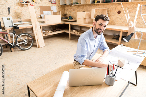 Photo  Cheerful youthful timber craftsman making drafts of product in workshop
