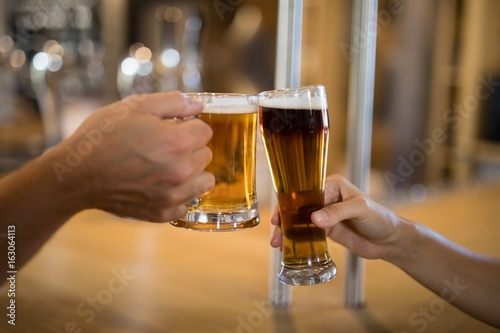 Couple toasting glass of beer at bar counter Canvas Print
