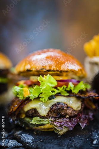 Fotobehang Restaurant Tasty smoked grilled and glazed beef burger with lettuce, cheese and bacon served with french fries on wooden table with copyspace, smoke mesquite timber wood in background.