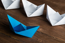 Business Leadership Concept With White And Color Paper Boats On Wooden Table