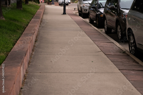 Paved sidewalk lined with parked cars in small downtown