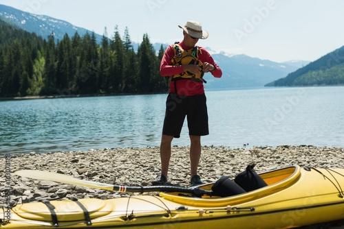 Man wearing life jacket while standing by kayak at lakeshore