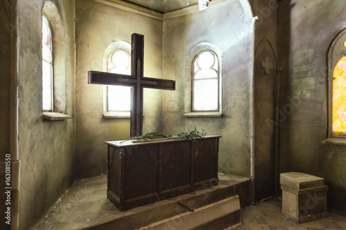 large Catholic cross opposite the windows near the wooden altar in abandoned chu Fotobehang