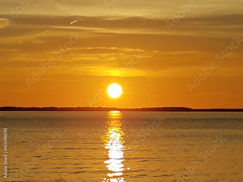 Staande foto Zeilen Sunset with full sun zoom with orange horizon and water reflection