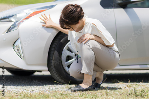young woman checking under a vehicle. Canvas Print