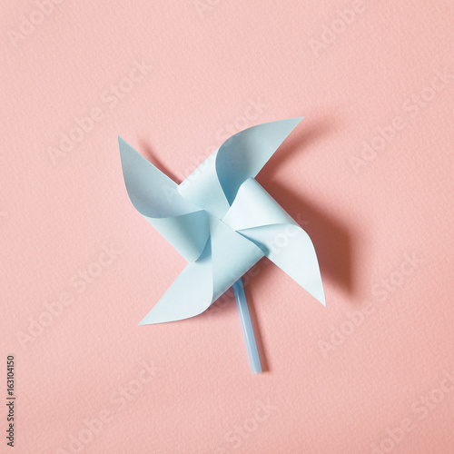 Vászonkép  Blue paper pinwheel on pink background