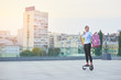 Woman holding shopping bags outdoor. Young female on hoverboard.