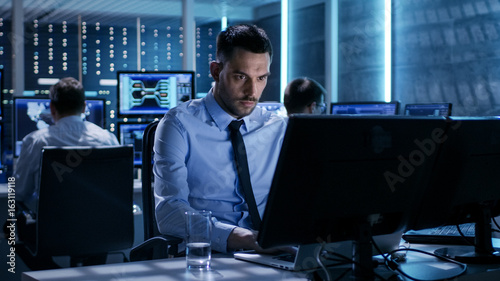 Fototapety, obrazy: Close-up of Technical Engineer Working on His Computer With Multiple Displays in Monitoring Room. In the Background His Colleagues with Graphics and Various Data on Their Monitors.