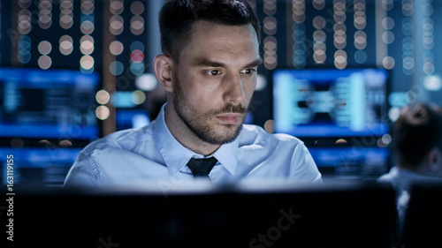Fototapety, obrazy: Close-up of a Professional Technical Controller Sitting at His Desk with Multiple Displays Before Him. In the Background His Colleagues Working in System Control Center.